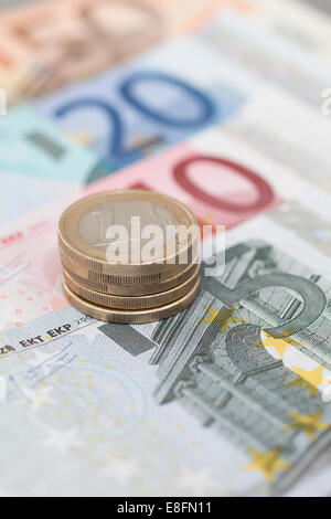 Stack of Euro coins on euro banknotes - Stock Photo