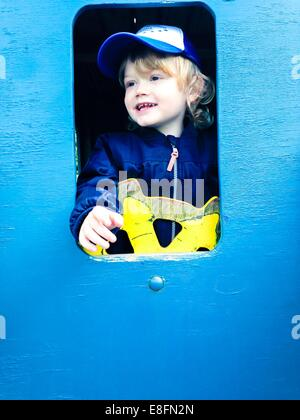 Boy playing on ship in the playground - Stock Photo