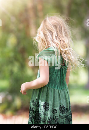 Rear view of girl (4-5) wearing green dress - Stock Photo