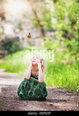 Girl sitting on a path looking at a butterfly - Stock Photo