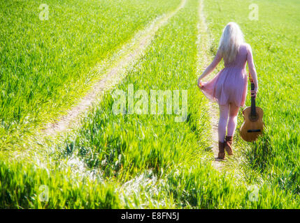 Rear view of young woman walking on green field with guitar - Stock Photo