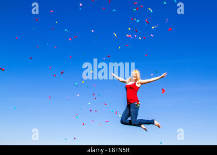 Portrait of blond woman jumping with confetti against blue sky - Stock Photo