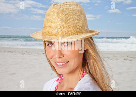Portrait of smiling woman on beach in straw hat, Cape Town, South Africa - Stock Photo