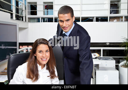 Portrait of smiling Businessman and Businesswoman in office - Stock Photo