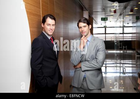 Two businessmen standing in office corridor - Stock Photo