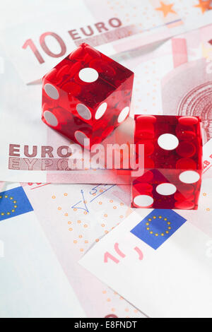 Two red dice on European banknotes - Stock Photo