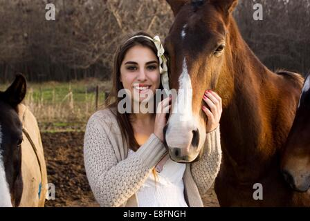 Argentina, Buenos Aires, Partido del Pilar, Manzanares, Portrait of teen (14-15) girl stroking horse - Stock Photo