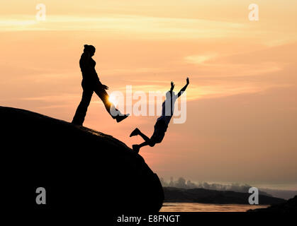 Silhouette of a man standing on rock kicking a woman - Stock Photo