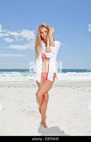 Young woman on beach standing in eagle yoga pose - Stock Photo