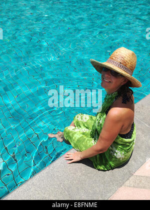 Portrait of woman sitting with feet in swimming pool - Stock Photo
