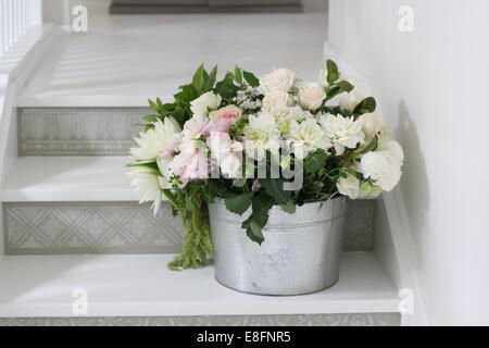 Bucket of cut flowers on steps - Stock Photo