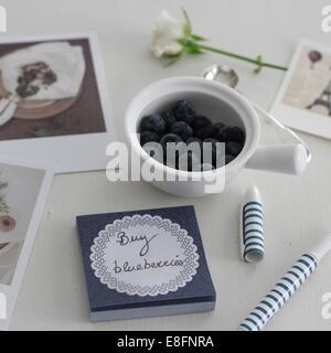 Blueberries in bowl beside hand written memo - Stock Photo