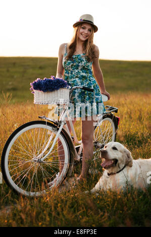 Young adult women standing with bicycle - Stock Photo