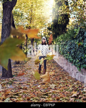 Woman standing throwing autumnal leaves in park - Stock Photo