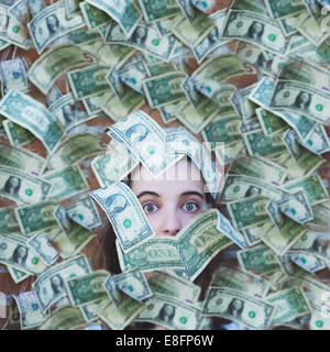 Portrait of a woman covered in American dollar bills - Stock Photo