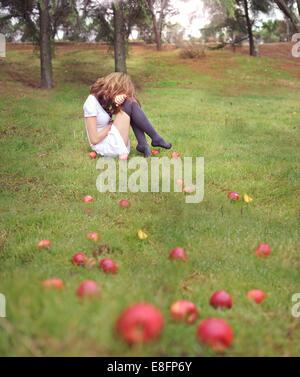 Woman sitting in a garden next to fallen apples, Spain - Stock Photo
