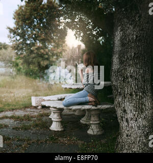 Woman sitting under a tree reading book with a steaming cup of tea on table, Spain - Stock Photo