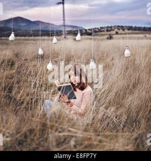 Woman reading book in field under low energy light bulbs suspended on wire - Stock Photo