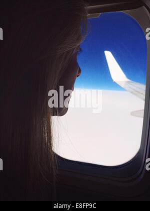 Woman looking out of window on a plane - Stock Photo