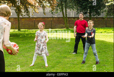 UK, West Midlands, Family with children (8-9), (10-11) ball game - Stock Photo