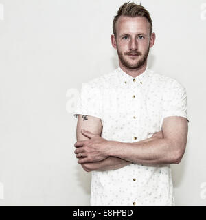 Portrait of man with his arms crossed - Stock Photo