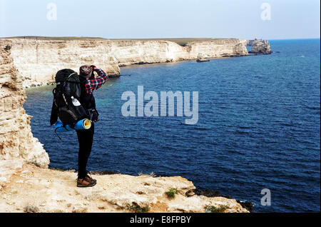 Hiker at cliff edge taking photograph of sea, rear view - Stock Photo