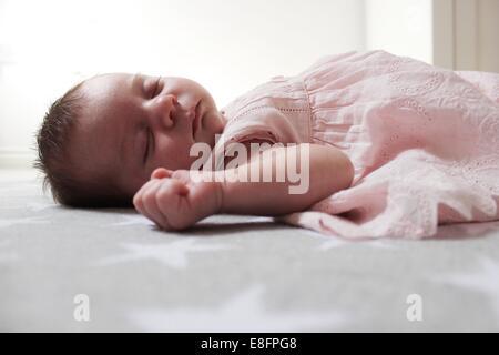 Baby girl lying on blanket sleeping - Stock Photo
