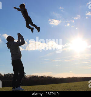 Father throwing son in the air - Stock Photo