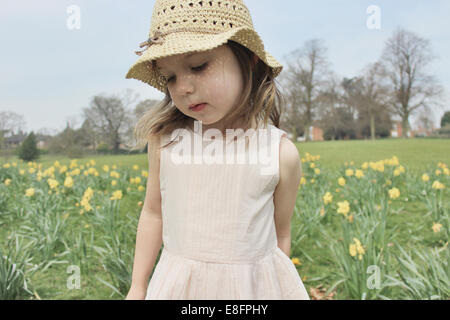 Girl wearing a straw hat standing in a field - Stock Photo