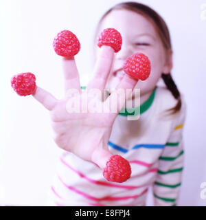 Girl with raspberries on her fingers - Stock Photo