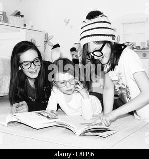 Portrait of three smiling girls reading books - Stock Photo