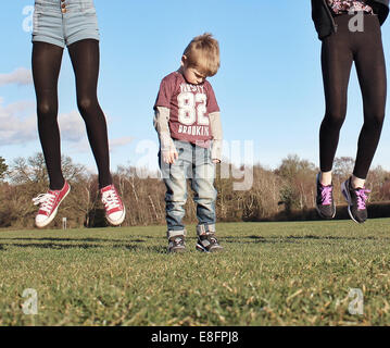 Boy sulking as two girls jump higher than he can - Stock Photo