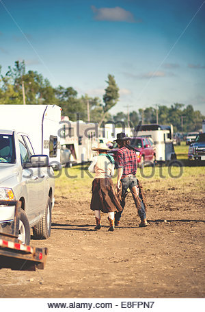 USA, Connecticut, Modern cowboy and cowgirl walking through yard at rodeo - Stock Photo