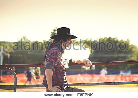 Cowboy leaning on fence and exhaling smoke - Stock Photo