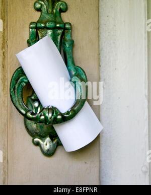 Note left on door knocker - Stock Photo