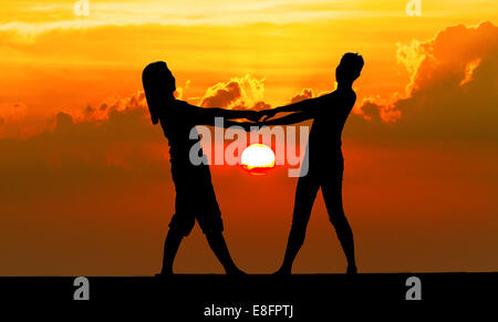 Silhouette of a Couple holding hands on beach at sunset, Thailand - Stock Photo