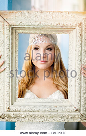 Bride holding picture frame - Stock Photo