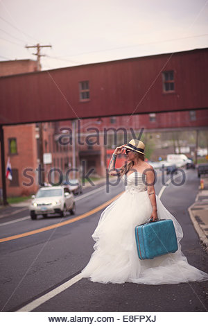 Bride standing on roadside - Stock Photo