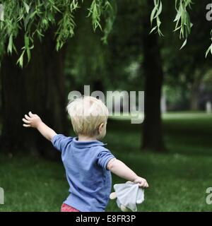 Rear view of little boy running in park with arms outstretched - Stock Photo