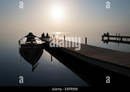 Silhouette of couple sitting at end of jetty by moored boat - Stock Photo