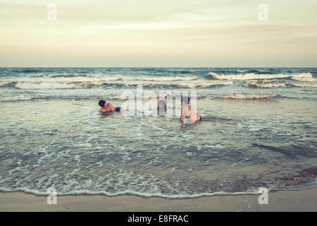 Three children playing in the ocean surf on beach, Barcelona, Spain - Stock Photo