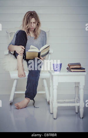 Portrait of a woman sitting on chair reading a book with cup of tea - Stock Photo