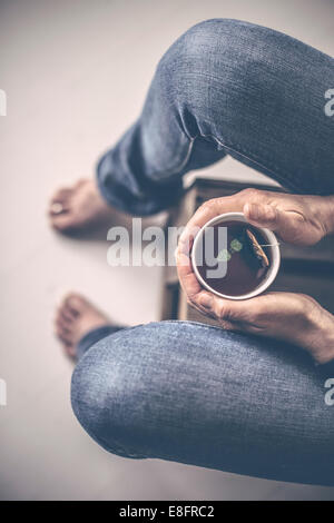 Overhead view of woman sitting with cup of tea - Stock Photo