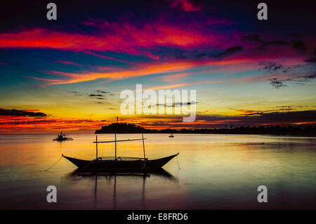 Philippines, Occidental Mindoro, Sablayan, Silhouette of boat at Sunset - Stock Photo