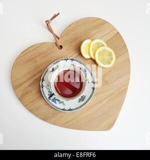Tea and lemon slices on a chopping board - Stock Photo