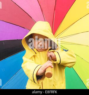 Boy in a raincoat holding a multi-colored umbrella - Stock Photo