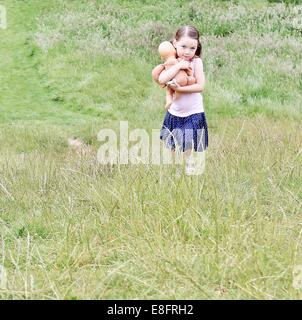 Girl walking through field carrying her doll - Stock Photo