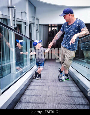 Father and son standing on a travelator - Stock Photo