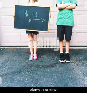 Girl (8-9) and boy (12-13) with blackboard sign - Stock Photo