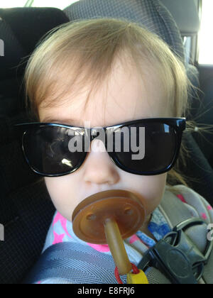 Portrait of girl (18-23 months) with dummy and sunglasses - Stock Photo